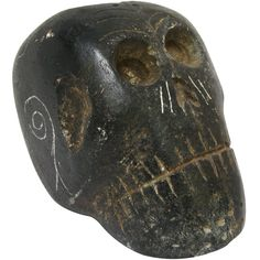 This is a fascinating artifact; a black steatite skull-shaped ceremonial pipe, made by the prehistoric Indian tribes who constructed the Etowah Mounds in Georgia. It is in very good condition, especially considering the fact that it was made over a thousand years ago. The skull form was carved from the rock and decorated with crude lines, swirls, and dots scratched into the surface. There is a large hole in the top of the skull to place smoking material and another at the back of the skull…