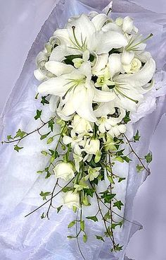 Brides Trailing wedding bouquet, White roses, white lilies and white singapore orchids.