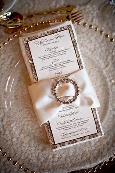 Crystal napkin ring around damask menu and napkins.