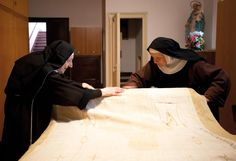 Nuns at a convent in Turin, Italy, unroll a cherished copy of the shroud made in 1644. Unlike this painted version, the original shroud shows no evidence of artificial pigments.