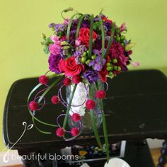 Cascade bouquet of hot pink roses, ageratum, purple carnations, lisianthus, globe amaranth and green hypericum berries by Beautiful Blooms b...