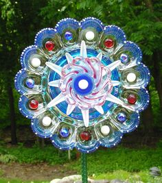Patriotic yard art made from upcycled egg plate, blue glass ash tray and other repurposed glass and marbles.
