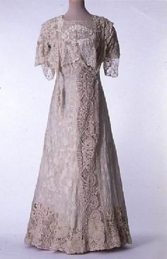 1900 Afternoon dress by Louise Emery, Paris. White silk taffeta embroidered in white silk; white chiffon; and re-embroidered bobbin lace on pink satin.