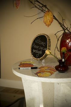 """Branches sticking out a glass vase provided an easy way to make a tree. Flickr member lutra98685 uploaded this to the OBB pool and explained that their guests hung fall """"leaves"""" for everyone to sign and then hang. The sign is a piece of log that was painted with chalkboard paint. """"A fun idea for any teacher."""""""