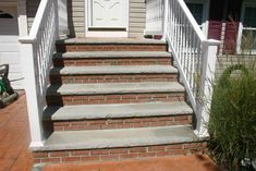 Masonry steps with limestone, brick veneers, and stamped concrete center landing.  Brick steps w/wooden railings?