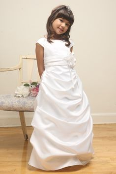 White Satin Bridesmaid Flower Girl Gown in SatinA gorgeous looking long draped skirt flower girl dress with off shoulder round neckline and a large floral accent