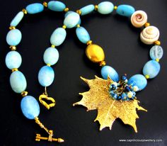 "Leaf on The Water    Calming blue Peruvian opals in a 21"" long necklace with a maple leaf electroplated leaf skeleton. A couple of sea shells and gold electroplated crystals, stardust beads and a brushed gold bead add interest, and a heart shaped toggle clasp provides a secure fastener. A froth of little crystal beads and faux pearls resemble the foam on the water.  £28.00"