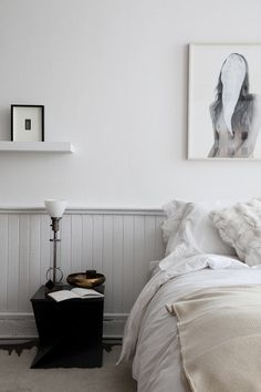 Mixed metals atop a modern cube-like table is a visual anchor point in an airy, white bedroom.