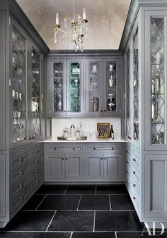 Designer Barbara Westbrook fashioned a gracious, party-ready home boasting two pantries for longtime clients in South Carolina. In the butler's pantry, diamond-pattern glass door fronts and a crystal chandelier lend a dressed-up look to the cabinetry | archdigest.com