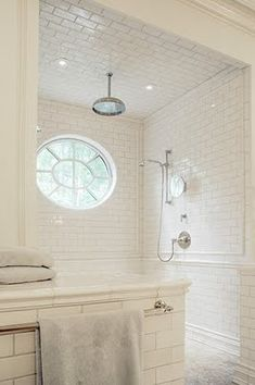 Subway tile with a small chair rail give this spacious shower a clean and classic look.  Love the round window letting in natural light and the rain shower.