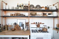 Copper pipe kitchen shelves make our hearts go pitter-patter!  Click through to see more of this inspiring kitchen space in an LA loft.