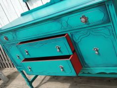 Tempting Turquoise just got irresistible. This moderately sized buffet has been glazed in the darkest of blues to give it the ultimate saturated hue. The inside in contrasting tomato red, original pulls in silver on silver gunmetal, two of which are backed with a bit of unexpected red. Modern Vintage.