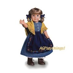 Kirsten's Checked Dress & Apron  Mama helped Kirsten choose the fabric and cut out the patterns for her gingham dress and yellow shawl. But the embroidered trim on her navy apron was Kirsten's idea! Also includes two navy blue hair ribbons. $22 KHOS  Released 1999 Z