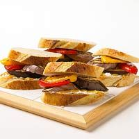 Grilled Eggplant and Sweet Pepper Sandwiches - Grills fire up when hot summer days shut down kitchens, and simple feasts, such as this Mediterranean stack of smoky eggplant and sweet peppers, are the rule.