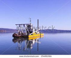 yellow dredging boat on trasimeno lake  - stock photo