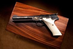 COLT MATCH TARGET WOODSMAN: This pistol sports elegantly checkered ivory grip panels. The full coverage engraving and muted gold accents flow smoothly over this long barreled gun, also fitted with an Elliason rear sight. This semi-automatic handgun blends the best of accuracy and beauty in a single package.