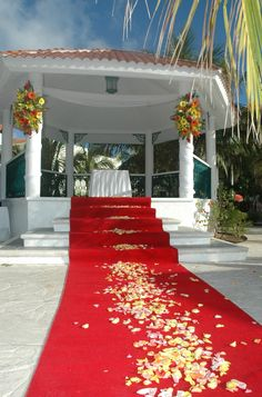 The red aisle runner coordinates extremely well with the floral colors, as well as the design of the gazebo.
