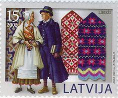 Latvian National Costumes. There are hundreds of different national costumes in Latvia, every region has its own. Uz pastmarkas attēloti lībiešu tautastērpi un rakstoti dūraiņi.