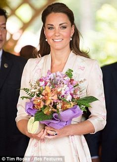 Elegant: Kate's outfit for the occasion matched perfectly right down to the flowers