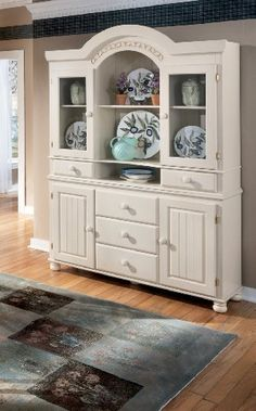 "Cottage Retreat White Dining Room Buffet and China Hutch by Famous Brand Furniture. $804.21. Buffet Inches: 55.35"" W x 16.22"" D x 30.94"" H. Hutch Inches: 56.5"" W x 15.79"" D x 49.21"" H. Rich antique finish.. Wood knobs.. Cream cottage and honey toned finish.. 5 working drawers.. Escape to the comfort of a country styled cottage with the ""Cottage Retreat"" dining collection. The rich antique finish of this country style furniture brings the true feeling of country to your..."