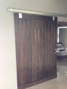 My husband made this barn door out of pine tongue & groove boards and hardware from the local Tractor Supply Store. Don't pay for expensive online barn door hardware when you can you purchase a box & rail system from Tractor Supply for less than half the cost of most online hardware. Looks great, works great! P.S. Minwax Jacobean stain is the color