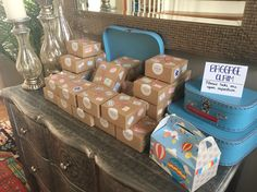"""The World Awaits / Travel theme Baby Shower - favor boxes with international postage stickers next to """"Baggage Claim: Please take one upon departure"""" sign. Baby Shower Table, Baby Shower Party Favors, Baby Shower Cards, Baby Shower Parties, Baby Shower Themes, Baby Boy Shower, Baby Shower Gifts, Shower Ideas, Bridal Shower"""