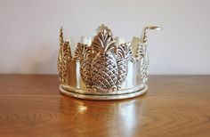 This is a beautiful silver plate wine or champagne bottle holder or dessous de bouteille featuring four trios of raised embossed pineapples,