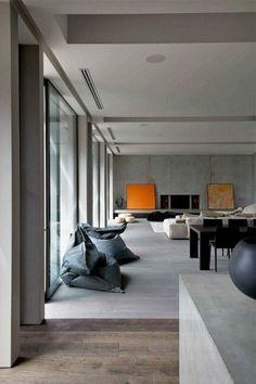 carrelage effet béton, poufs gris, table et chaises noires