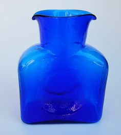 A nice Blenko water pitcher shape 384 in a dark cobalt blue color. This water pitcher has a pour spout on each side for pouring water. It measures tall by wide by deep. Nice and clean. Perfect to use as a pitcher or carafe. Blenko Glass, Water Pitchers, Blue Art, Carafe, Cobalt Blue, Glass Art, Vase, Deep, Shapes