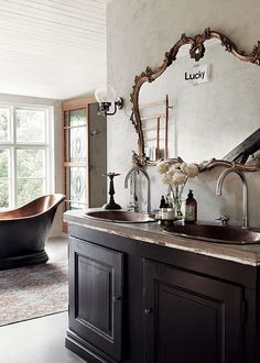ornate mirror above vintage cabinet . Free standing bath tub. his and hers sinks . Black bathroom . sfgirlbybay