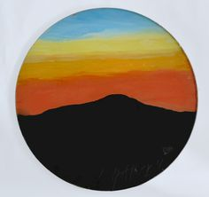 Rest - Circular surface.  A mountain range in silhouette, at sunset. Orange…