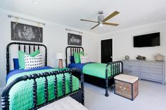 Charming blue and green shared boys' room features reclaimed wood trunks placed in front of black Jenny Lind Beds dressed in blue and green bedding and positioned under plumbing pipe and rope art displays. Green Boys Room, Green Rooms, Bedroom Green, Bedroom Decor, Bedroom Ideas, Shared Boys Rooms, Little Boys Rooms, Big Boy Bedrooms, Guest Bedrooms