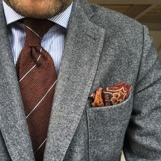 Love this combination of a gray jacket, deep burnt orange necktie, striped shirt, and patterned orange pocket square
