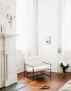 home of interior designer elizabeth damrich via domino   beautiful white fireplace and hard wood floors   white armchair with a modern industrial metal frame   Get inspired and make the look your own with an IKEA PS armchair with a white Bemz cover