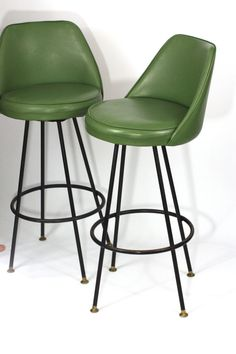 These two green midcentury modern vinyl swiveling bar stools are in great vintage used shape from the 1960s. The black paint is a little worn off