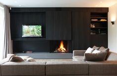 Panel slides to hide TV when not in use, built-in storage around modern fireplace in dark wood
