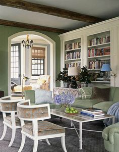 On the opposite wall of the family room, the low backs of klismos chairs allow those on the sofa a view of the cozy fire. Wall covering and sage green upholstery is Peter Fasano's Laundered Linen in grass.   - HouseBeautiful.com