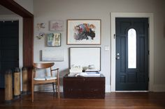The open front room of Rachael's home features art made by friends, vintage furniture, and quirky decorative objects like antique practice artillery shells.