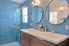 Remodeled Bathroom with sea blue tiles, dark wood custom cabinets, double oblong sinks and 2 round chrome mirrors recreated this mid- century bathroom