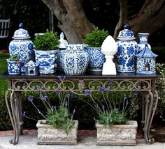 Gathering of pert blue and white china on an ornately styled wrought iron table.