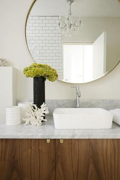 Bathroom with medium wood tones, marble counter. Large round mirror - desire to inspire