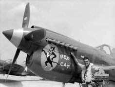 Portrait of 280843, Squadron Leader Clive Gardiner Tolhurst, of Adelaide, SA, Commanding Officer of 75 Squadron, RAAF, standing with his P40 Kittyhawk with the nose art depicting 'Hep Cat'. Netherlands East Indies: Halmahera Islands, Morotai. March 1945.