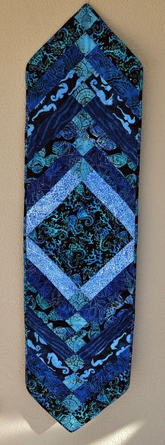 Beautiful blue batiks were used to make this quilted reversible table runner. The theme is the seashore with fabrics featuring seahorses,