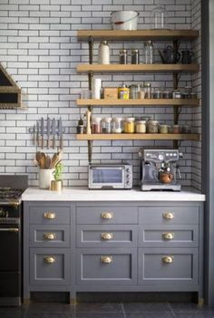I really like the grey cabinets and brass pulls. Kitchen in a New York apartment with grey cabinets with brass pulls, wall mounted shelves, marble countertops and subway tile walls on dark . Blue Gray Kitchen Cabinets, Farmhouse Kitchen Cabinets, Grey Kitchens, Modern Farmhouse Kitchens, Home Kitchens, Kitchen Backsplash, Kitchen Shelves, Backsplash Ideas, Kitchen Storage