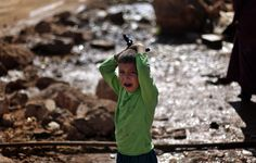 A Syrian boy who fled with his family from the violence in their village, cries as he waits to fill water at a displaced camp, in the Syrian village of Atma, near the Turkish border with Syria, Monday, Nov. 5, 2012. (AP Photo/ Khalil Hamra)