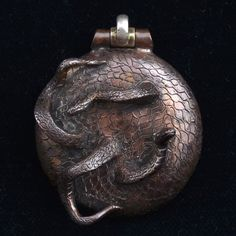 A great example of Bob;s wax working genius. Two sneaky snakes are popping into and out of a disc covered by a snakeskin pattern. The bail at the top is sterling and hinged. 32.3 grams 40 mm circumference 12 mm high at tip of snakey nose Designed and produced by Robert Burkett.