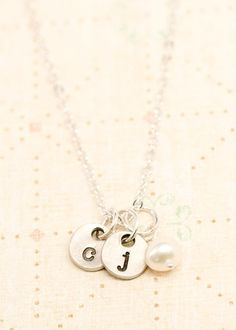 even cuter than the pottery barn necklace! a charm with r, one with m, one with (insert babys initial here), and a pearl--LOVE