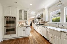 Traditional Kitchen with Complex granite counters, Flush, Glass panel, Raised panel, Subway Tile, L-shaped, Hardwood floors