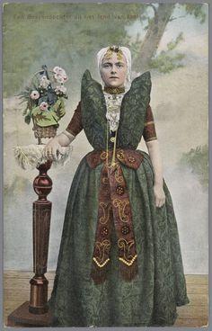 Vrouw in Axelse streekdracht. De vrouw draagt over de ondermuts en het oorijzer een 'trekmuts'. Ze draagt 'dubbele strikken' (dubbele, klaverbladvormige gouden oorijzerhangers) aan de 'krullen' (oorijzeruiteinden) van het oorijzer. Tussen de 'krullen' zijn twee gouden mutsenspelden in de muts gestoken. 1905-1908 #Zeeland #Axel