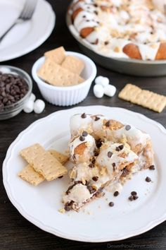 Crushed graham crackers, mini chocolate chips, and mini marshmallows are rolled up in buttery cinnamon sugar rolls to create this S'mores Cinnamon Roll Cake. Top it all off with a marshmallow frosting and extra toppings for a delicious dessert! On MyRecipeMagic.com
